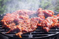 Grilling pork steaks on barbecue grill selective focus Stock Photography
