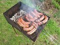 Grilling sausages on barbecue grill beef bratwurst over a fire Royalty Free Stock Photo
