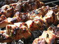 Tasty Grilling shashlik is cooked on fire. Grilled meat. Royalty Free Stock Photo