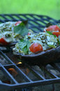 Grilling stuffed Portobello mushrooms on outdoor grill Royalty Free Stock Photo