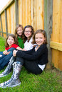 Grils group in a row smiling in a wooden fence sitting outdoor Royalty Free Stock Photo
