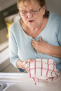 Grimacing senior adult woman kitchen sink chest pains Royalty Free Stock Photography