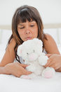 Grimacing young woman playing with a teddy bear Royalty Free Stock Photo