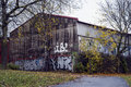 Grimy old house by autumn an worn building with grafitti in an landscape Royalty Free Stock Photography