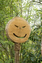 Grinning face on tree pit mouth and eyes wooden sign in park Royalty Free Stock Photography
