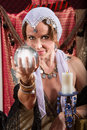 Grinning fortune teller female holding a crystal ball Stock Images