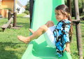 Grinning girl on a slide little in blue black white t shirt and white shorts playing green with swing behind Royalty Free Stock Photo