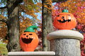 Grinning jack o lanterns on wall two set old stone to scare halloween trick or treaters with colorful fall foliage beyond Stock Photo