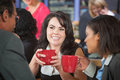 Grinning woman with coffee and coworkers women in bistro Stock Image
