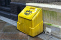 Grit salt yellow plastic box on street pavement Stock Image