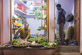 Grocer and customer varanasi india february sitting on ground with standing in doorway small vegetable shop on street market Royalty Free Stock Photography