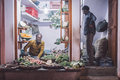 Grocer and customer varanasi india february sitting on ground with standing in doorway small vegetable shop on street market post Royalty Free Stock Photo