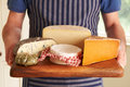 Grocer holding board with selection of luxury cheeses holds Royalty Free Stock Photography