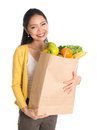 Groceries shopping happy smiling young pan asian woman holding paper bag full of isolated on white background Stock Image