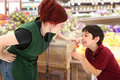 Grocery Clerk Giving Child Cherries in Store Royalty Free Stock Photo