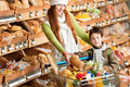 Grocery shopping store - Happy woman with child Stock Photos
