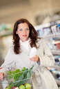 Grocery shopping store  Young woman buying shampoo Royalty Free Stock Photography