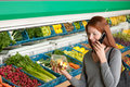 Grocery store - Red hair woman with mobile phone Royalty Free Stock Photo