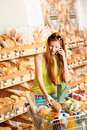 Grocery store: Red hair woman with mobile phone Royalty Free Stock Photo