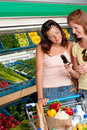 Grocery store - Two women with mobile phone Royalty Free Stock Photo