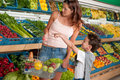 Grocery store - Woman with child buying vegetable Royalty Free Stock Photos