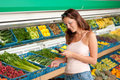 Grocery store - Woman holding mobile phone Royalty Free Stock Photo