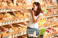 Grocery store: Young woman holding mobile phone Royalty Free Stock Photo