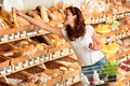 Grocery store: Young woman holding shopping basket Royalty Free Stock Photo