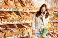 Grocery store: Young woman with mobile phone Royalty Free Stock Photo