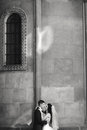 Grom huging kissing bride with red hair near wall outdoors Lviv Royalty Free Stock Photo