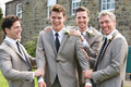 Groom with best man and groomsmen at wedding smiling to camera Royalty Free Stock Image