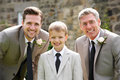 Groom with best man and page boy at wedding smiling to camera Royalty Free Stock Image