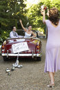 Groom with bride in car throwing bouquet towards woman happy convertible Stock Photos