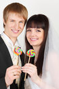 Groom and bride hold colorful lollipops Royalty Free Stock Photos