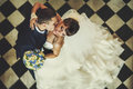 Groom and bride is kissing on the background checkered floor Royalty Free Stock Photo