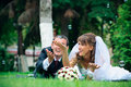 Groom and bride lie on a grass around soap bubbles Stock Photo