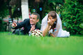 Groom and bride lie on a grass around soap bubbles Royalty Free Stock Photo