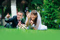 Groom and bride lie on a grass around soap bubbles Stock Photos