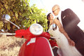 Groom and bride next to a red scooter near Stock Photography