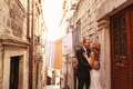Groom and bride outdoors on a narrow street on their wedding day Royalty Free Stock Photo