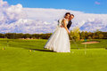 Groom and bride playing golf Royalty Free Stock Photo