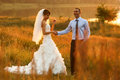 Groom  and  bride is posing on the background beautiful sunset o Royalty Free Stock Photo