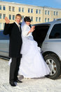 Groom and bride stand near wedding limousine Royalty Free Stock Photos
