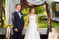 Groom and bride under decorative wedding arch Royalty Free Stock Photo
