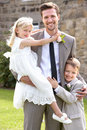 Groom with bridesmaid and page boy at wedding smiling to camera Royalty Free Stock Images