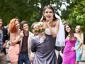 Groom carries his bride over shoulder outdoor Royalty Free Stock Photos