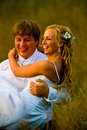 Groom carrying bride in field Royalty Free Stock Photo