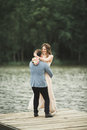 Groom carrying bride near lake and forest Royalty Free Stock Photo