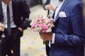 Groom with flowers in suit holding wedding bouquet Royalty Free Stock Photo