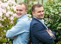 Groom and friend standing back to back at park closeup portrait of Royalty Free Stock Images